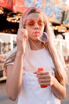 Garota de tiro médio fazendo balões de sabão