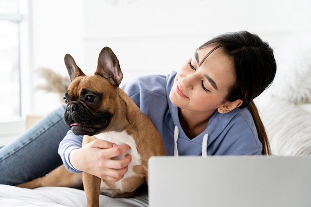 Garota de tiro médio olhando para um cachorro