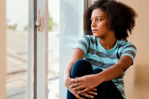 Garota de tiro médio olhando pela janela