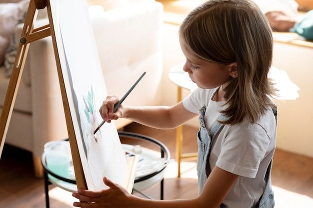 Garota de tiro médio pintando com pincel