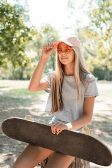 Garota de tiro médio posando com skate