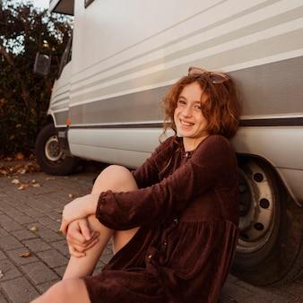 Garota de tiro médio posando perto de van
