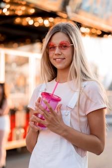 Garota de tiro médio segurando bebida
