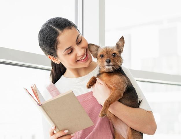 Garota de tiro médio segurando cachorro e livro