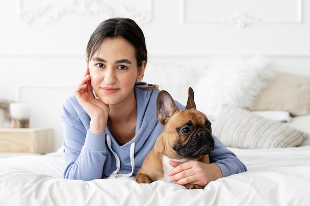 Garota de tiro médio segurando cachorro na cama