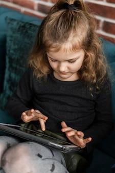 Garota de tiro médio segurando tablet