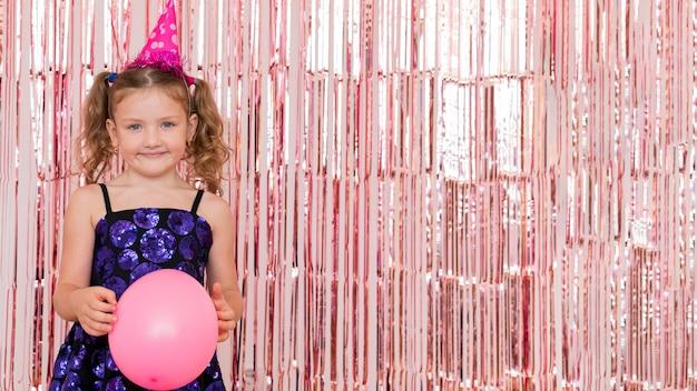 Garota de tiro médio segurando um balão rosa