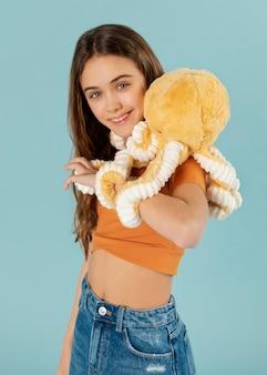 Garota de tiro médio segurando um brinquedo de polvo