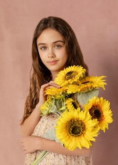 Garota de tiro médio segurando um buquê de flores