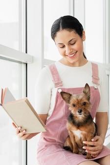 Garota de tiro médio segurando um livro e um cachorro