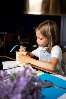 Garota de tiro médio sendo criativa com papel