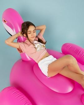 Garota de tiro médio sentada em um flamingo inflável