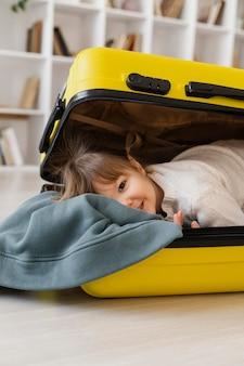 Garota de tiro médio sentada na bagagem