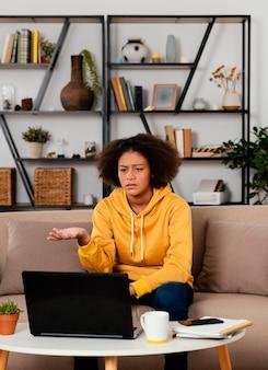 Garota de tiro médio sentada no sofá