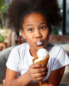 Garota de tiro médio tomando sorvete