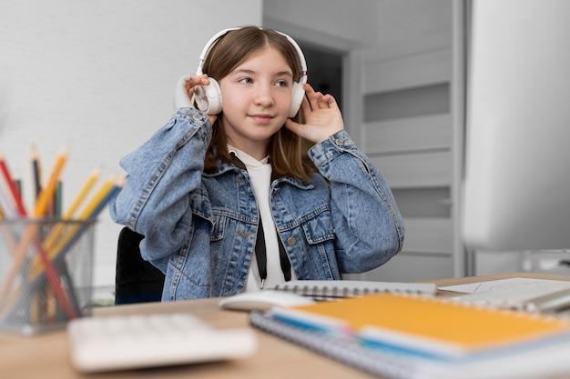 Garota de tiro médio usando fones de ouvido