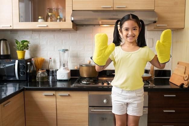 Garota de tiro médio usando luvas de cozinha