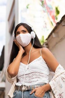 Garota de tiro médio usando máscara e fones de ouvido