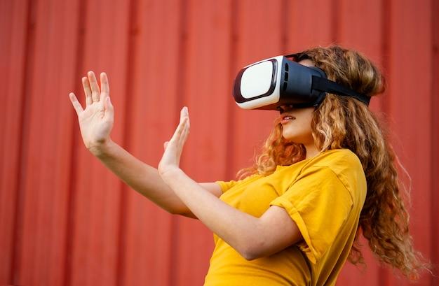 Garota de tiro médio usando óculos de realidade virtual