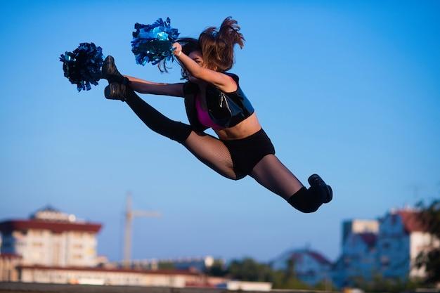 Garota de torcida com pompons executa elemento acrobático ao ar livre no telhado
