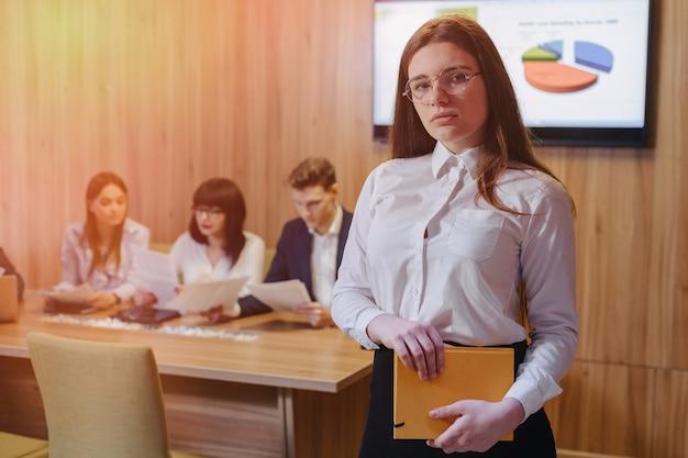 Garota de trabalhador de escritório elegante jovem atraente em copos com um notebook nas mãos no fundo dos colegas de trabalho