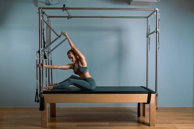 Garota de treinador de paladares posando para um reformador no ginásio. conceito de fitness, equipamento especial de fitness, estilo de vida saudável, plástico