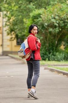 Garota de turista com mochila de lona, olhando para trás na rua