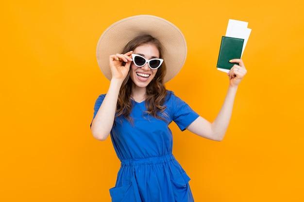 Garota de turista com passaporte e bilhetes no fundo de uma parede laranja sorrindo