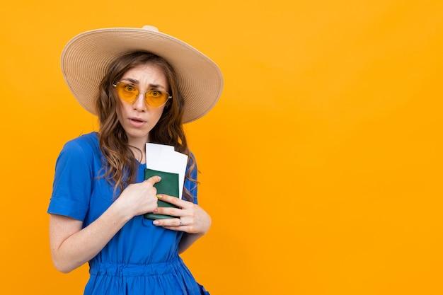 Garota de turista com um passaporte e brancos contra uma parede amarela, pressiona documentos no peito