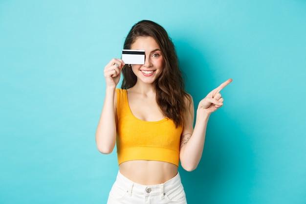Garota de verão elegante com cartão de crédito apontando para o lado, mostrando seu logotipo no espaço de cópia do lado direito, em pé contra um fundo azul