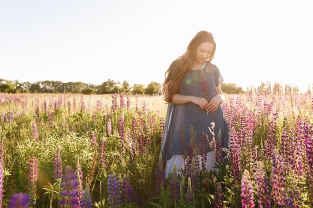 Garota de vestido azul andando no campo de flores.