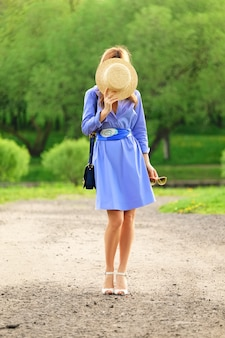 Garota de vestido azul cobre o rosto com um chapéu