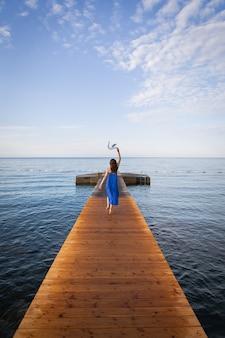 Garota de vestido azul corre em um píer de madeira perto do mar. montenegro, budva