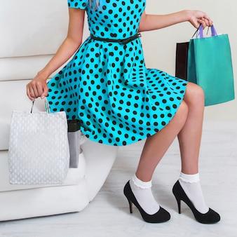 Garota de vestido azul e sapatos pretos com sacos de compras em um fundo branco. sexta-feira preta