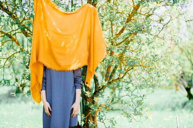 Garota de vestido azul, se escondendo atrás de cobertor laranja na árvore