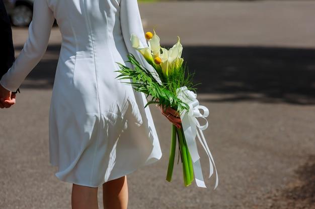 Garota de vestido branco com um buquê de flores e verde contra