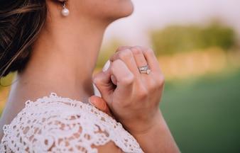Garota de vestido branco e com brincos brancos, segurando as mãos perto do pescoço