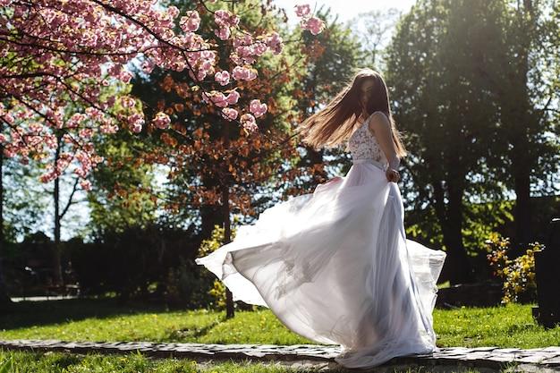 Garota de vestido branco fica sob rosa florescendo árvore de sakura no parque