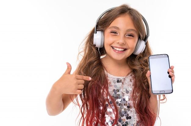 Garota de vestido brilhante, com grandes fones de ouvido brancos, ouvindo música e apontando para smartphone preto isolado