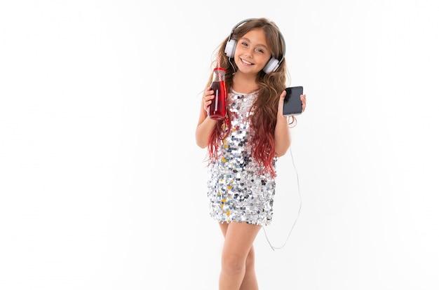 Garota de vestido brilhante, com grandes fones de ouvido brancos, ouvindo música, segurando o smartphone preto