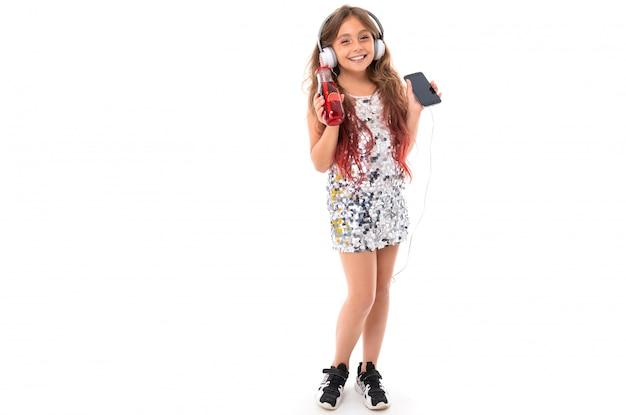 Garota de vestido brilhante e tênis pretos, com grandes fones de ouvido brancos, ouvindo música, segurando o smartphone preto e garrafa de plástico vermelha com bebida vermelha e pinça isolada