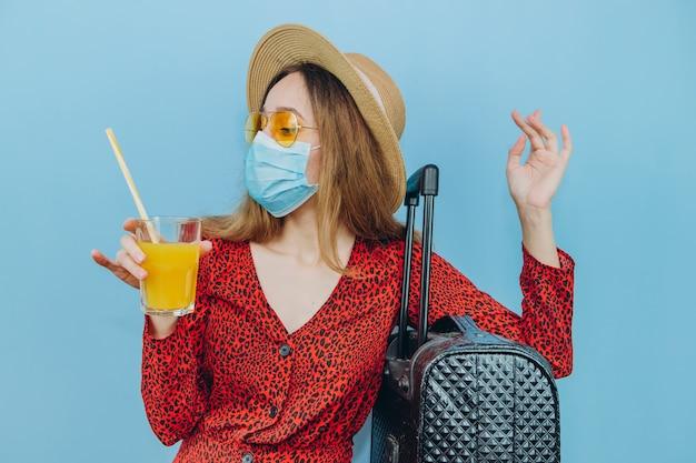 Garota de vestido, chapéu e óculos de sol com máscara médica no rosto e coquetel nas mãos dela.
