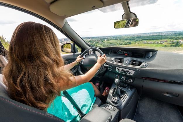 Garota de vestido com cabelo vermelho, dirigindo um carro