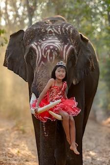 Garota de vestido extravagante, felizmente sentado em um marfim