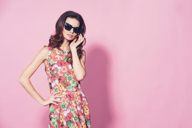 Garota de vestido floral e óculos de sol posando