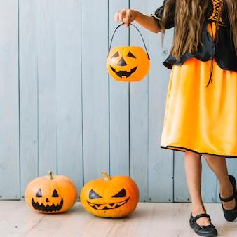 Garota de vestido preto e laranja em pé e segurando a cesta de halloween