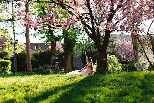 Garota de vestido rosa senta-se sob a árvore de sakura florescendo no parque