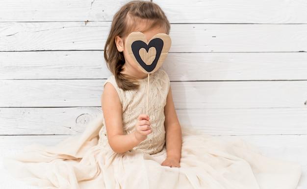 Garota de vestido, sentado na parede de madeira branca com um coração nas mãos