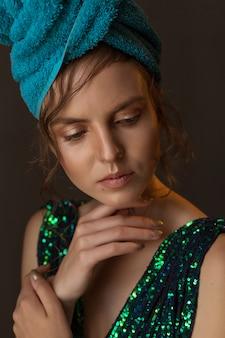 Garota de vestido verde-azul brilhante e toalha na cabeça