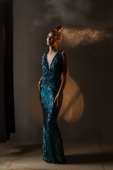 Garota de vestido verde-azul brilhante está de pé na luz quente, fumaça,